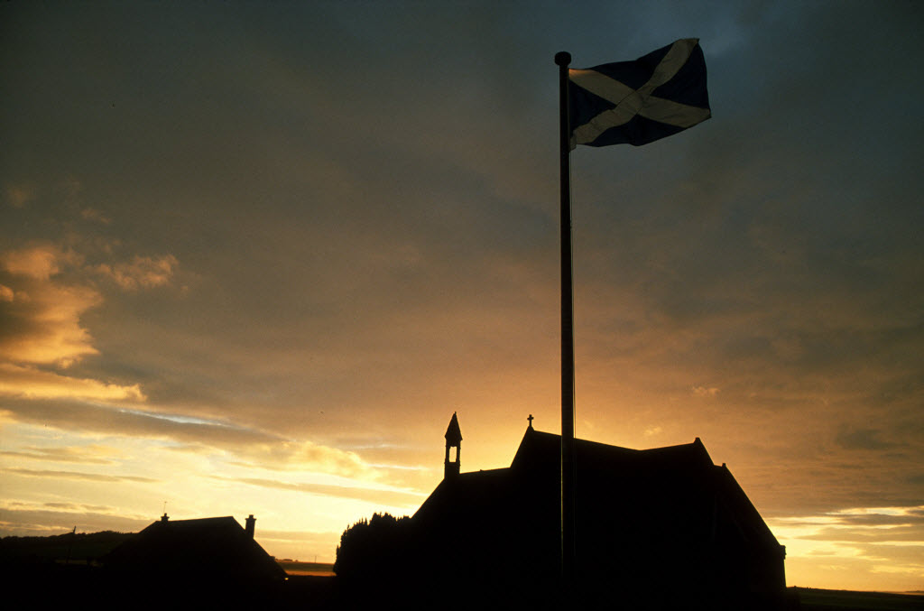 The Saltire flies at sunset at Athelstaneford Church (The Churc of Plaque) as it was here that the St. Andrew's cross (The Saltire) was first adopted as a Scottish symbol, north east of Haddington, East Lothian.