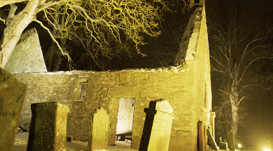 The atmospheric Alloway Kirk floodlit at night , Ayrshire.