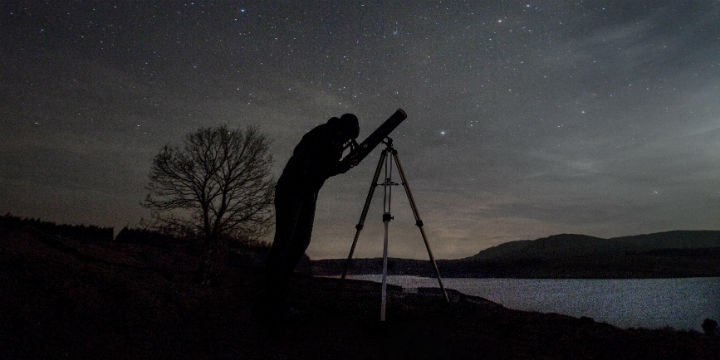 A silhouette of a stargazer by a loch who is looking through a telescope, with starry sky beyond
