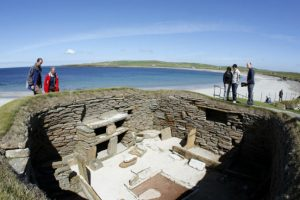 Visitors look into a Stone Age settlement in Skara Brae, Orkney