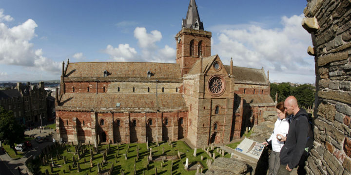 Visitors look onto the red stone exterior and cemetery of St Magnus Cathedral, in Kirkwall