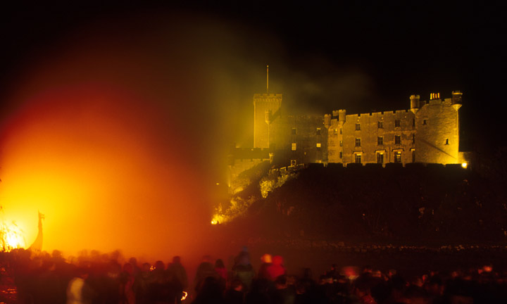Crowds watch as a bonfire glows and lights up a viking boat and the castle.