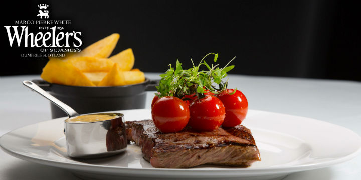 Close up of a steak served with tomatoes and chips at Wheeler's of St James's, Dumfries