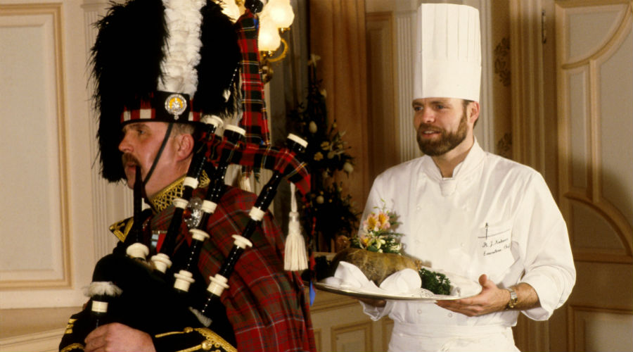 A piper in full Highland regalia pipes in the haggis