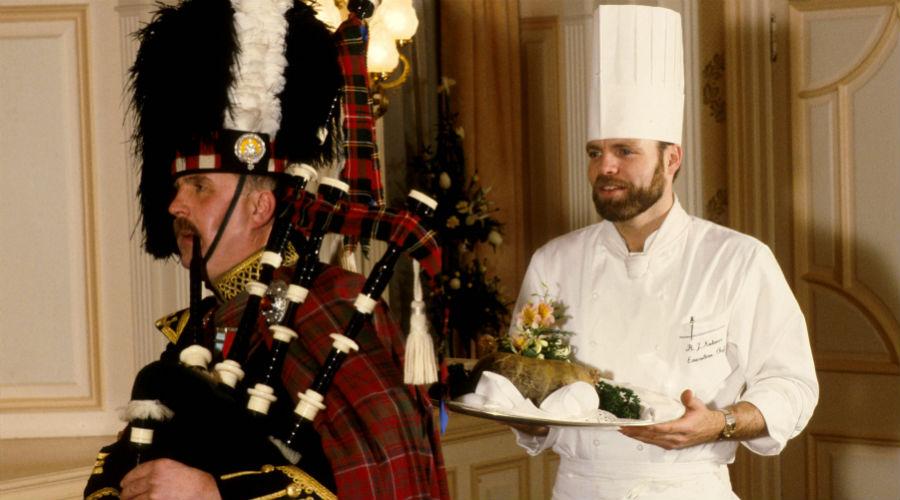 A piper in full Highland regalia pipes in the haggis