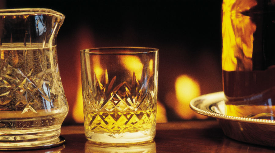 A dram of whisky in a cut crystal glass with a log fire flickering warmly behind