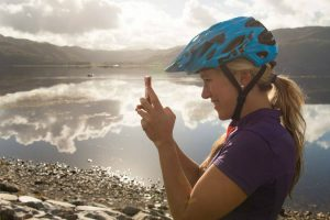 Hannah Barnes pauses at a loch side on her journey through the North West Highlands. Image credit Andy McCandlish
