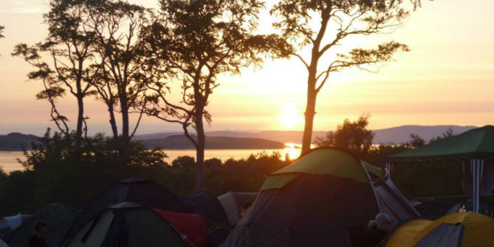 looking over a campsite and past trees to sunset over islands in the distance.
