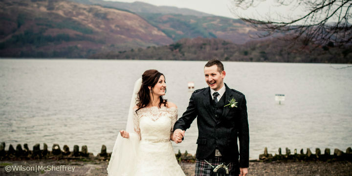 The wedding couple stand holding hands with a loch and hills behind them