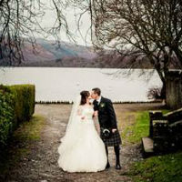 The wedding couple share a kiss with Loch Lomond in the background.