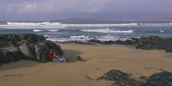 A couple shelter on a rocky beach and look out to the Sound of Taransay, Isle of Harris