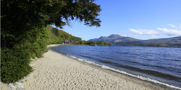 looking along a stretch of deserted beach and down the loch to hills beyond