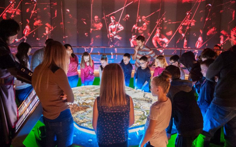 A group of children gathered round the 3D map at the Battle Room at the Battle of Bannockburn Visitor Centre