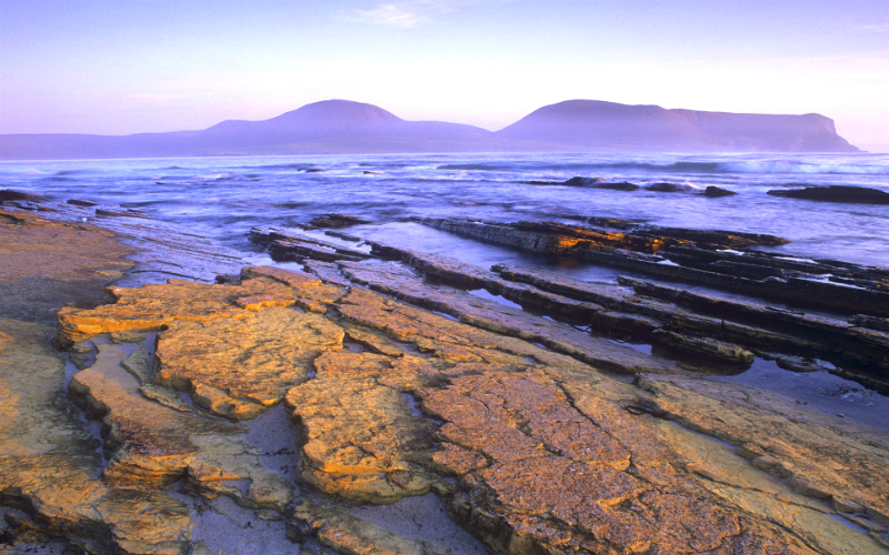 Looking across Arebeth Beach to the Island of Hoy at sunset, Orkney