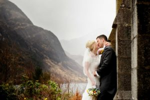 A wedding couple kiss with misty hills in the distance