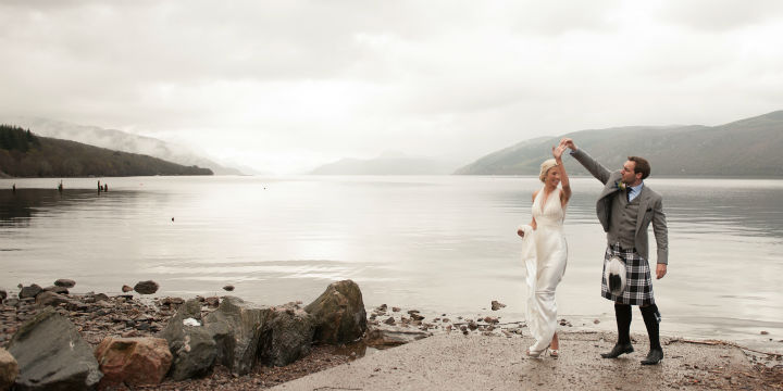 A wedding couple dance by the calm shore of the loch