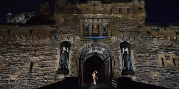 A wedding couple embrace at the grand castle entrance