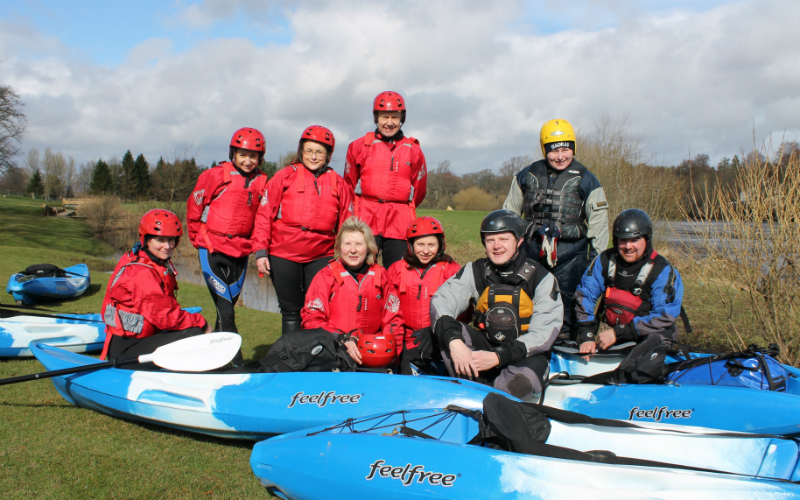 A group of kayakers pose on the banks of the River Tay