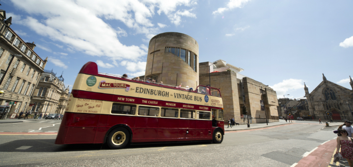 A MacTours Sightseeing Bus on George IV Bridge with the National Museum of Scotland visible beyond, in the city centre of Edinburgh