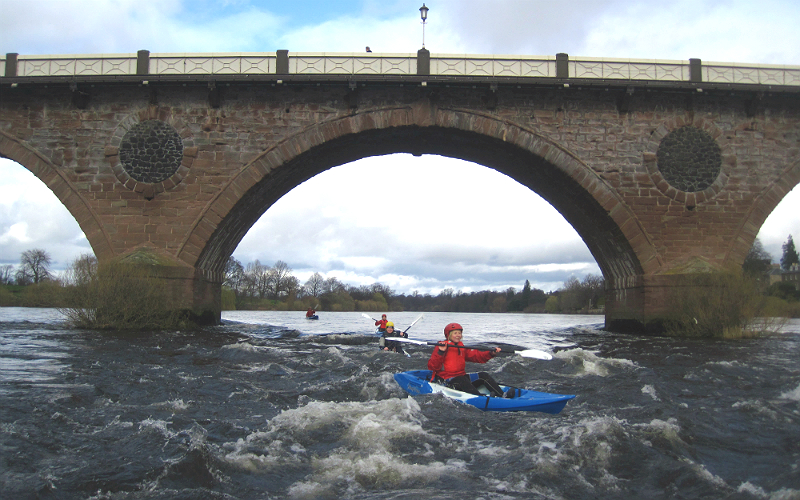 Kayakers paddle through waters under a bridge on the River Tay