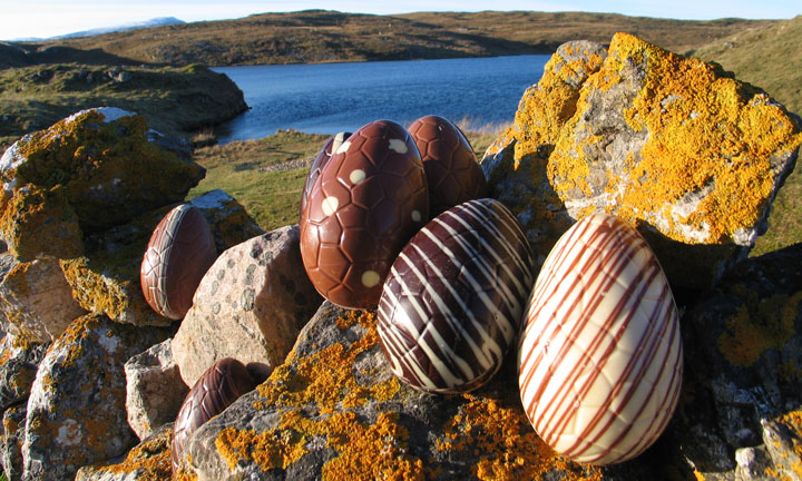 Patterned chocolate eggs displayed on rocks with water in the background.