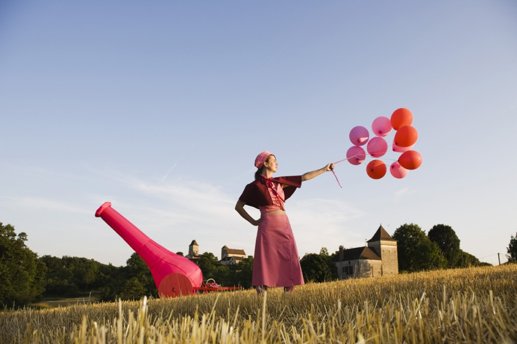 A woman stands in a field holding aloft a bunch of pink balloons. Behind here there is a pink canon.