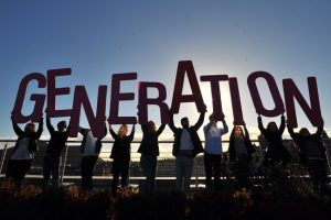 People hold up large letters which spell out Generation against clear sky.