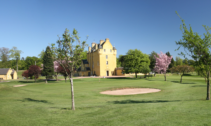 A parkland course with the striking yellow castle walls in the background.