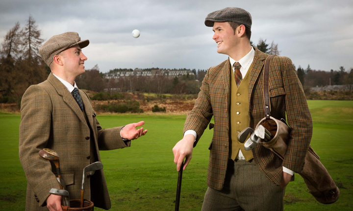 Two men in flats caps and tweed stand by the course with hickory clubs and balls.