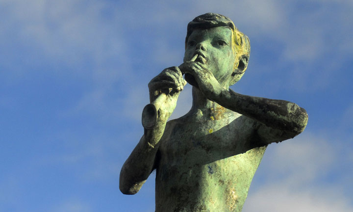 Looking up to a bronze statue of a boy playing a whistle.