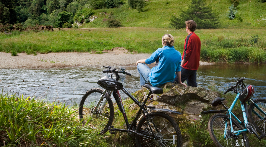 Cyclists stop to enjoy the views across the River Tweed