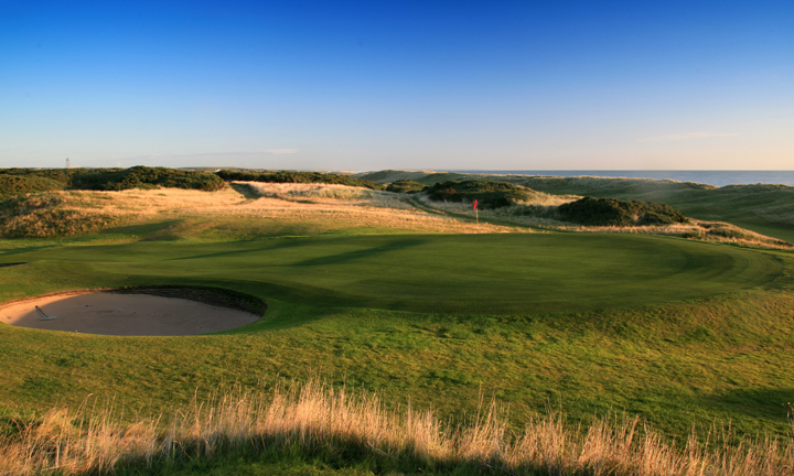 A flag and hole in the midst of undulating greens and golden dunes