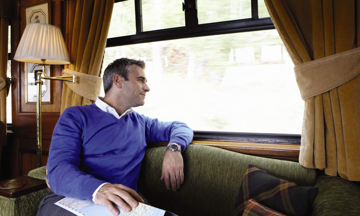 A man relaxes on a sofa as he admires the view in the Royal Scotsman Observation Lounge