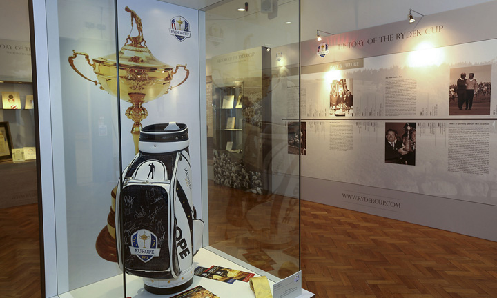 A signed 2012 tour golf bag on display with an exhibition wall behind.
