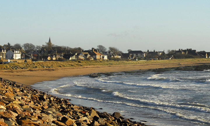 Looking along a stretch of beach with the town beyond.