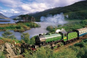 A steam train crossing the West Highland Line with Loch Eilt in the background