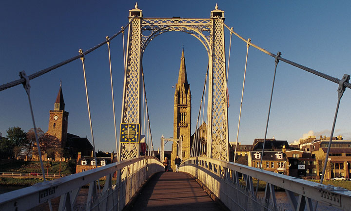 Looking over the suspension bridge across the river ness to the spire of the high church