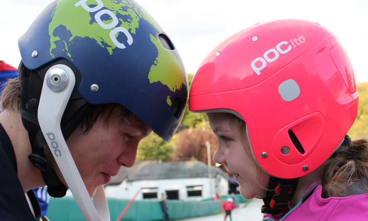 A girl and boy face each other head to head in their crash helmets.