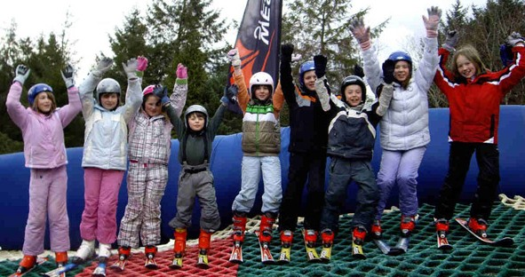 Children stand on a ski slope waving their hands in the air