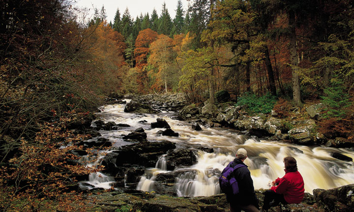 Two walkers pause a moment to look over the tumbling water of the hermitage falls in the course of the River Braan in woodland near Dunkeld, Perthshire