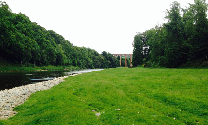 Looking down the river as it curves round a stretch of grass, with the viaduct beyond.