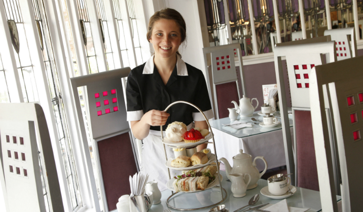 A waitress smiles as she serves afternoon tea at the Mackintosh-designed Willow Tearooms on Sauchiehall Street, Glasgow
