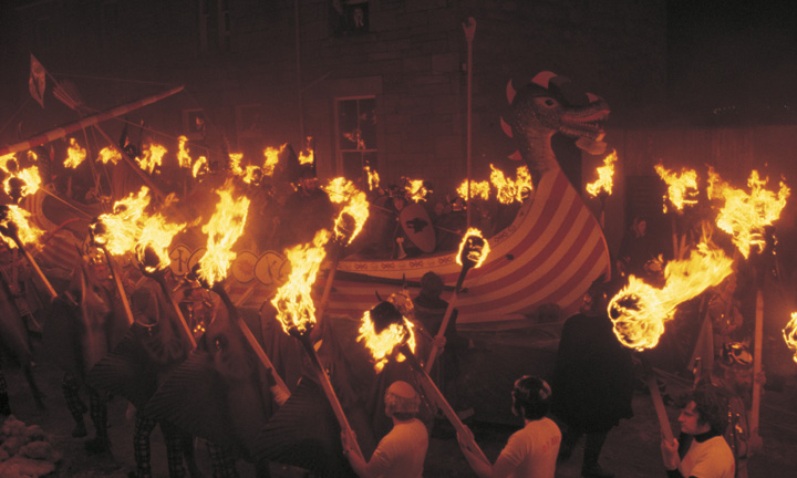 Men with lit torches surround a replica Viking ship.