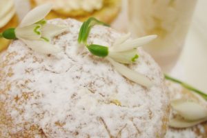 A close-up of a scone dusted with icing suger and decorated with snowdrops.