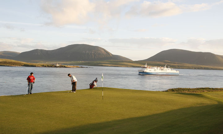 Two men play golf as the ferry passes in the distance.