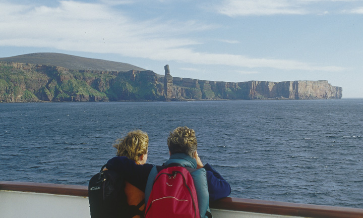 Two passengers on deck admire the sea stack and cliffs.