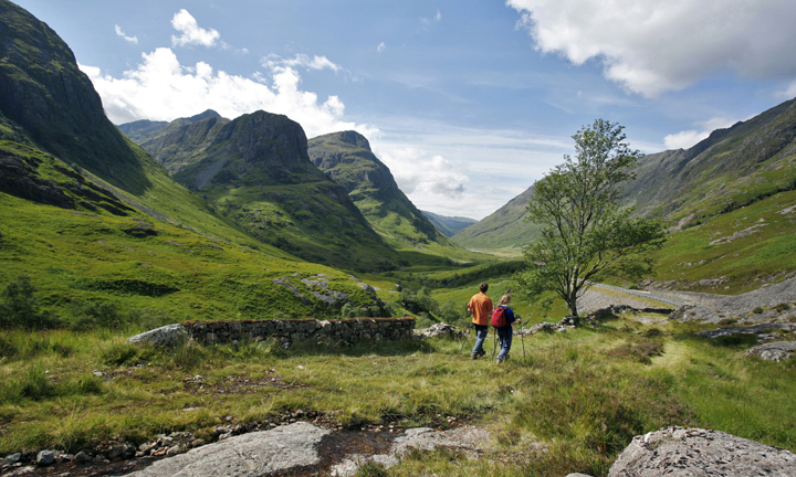 A couple walking on the old drovers road in Glen Coe with the famous 'three sisters' of Glen Coe in the background.