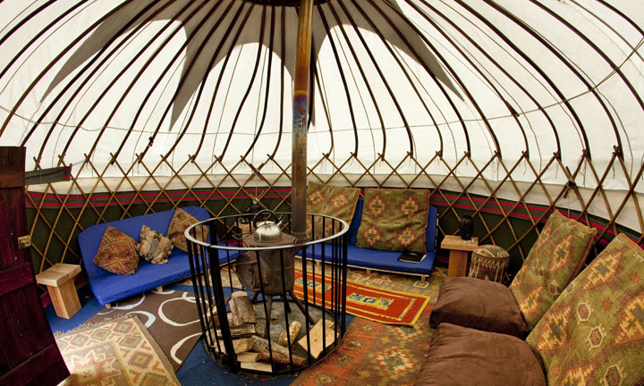 The interior of a yurt, with cushions on the floor and a log fire in the centre.