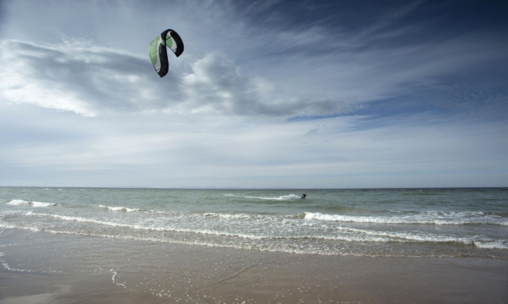A kite surfer in the waves on a windy day.