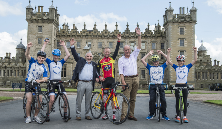 Team Raleigh cyclist Evan Oliphant at Floors Castle stands with his bike and companions.